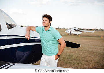 Smiling man standing near small airlane - Smiling attractive...