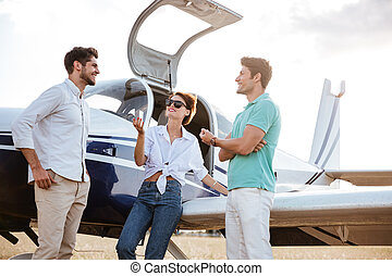 Happy friends standing and talking near small plane - Three...