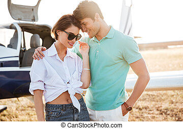 Couple standing and hugging near small airplane - Beautiful...