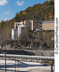 Limestone or crushed stone factory in wooded valley -...