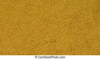Millet grains falling on a pile of millet