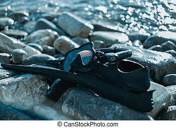 Outfit of freediver on pebble coast near the sea, flippers...