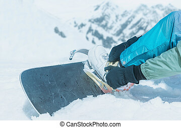 Man putting on his snowboard outdoor - Unrecognizable man...