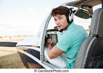 Man pilot sitting in cabin of small airplane - Attractive...