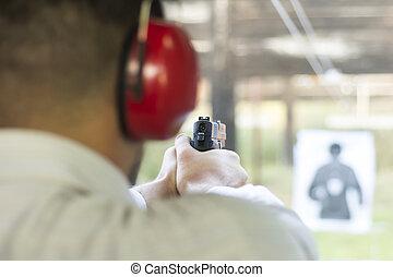 Shooting with Gun at Target in Shooting Range. Man...