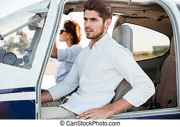Young pilot and beautiful stewardess sitting inside airplane...