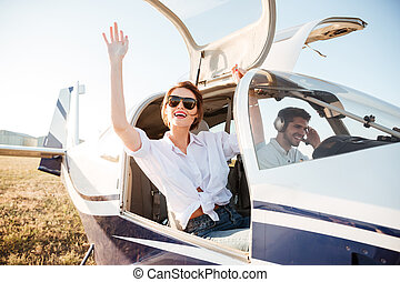 Woman in sunglasses waving from the plane cabin after...