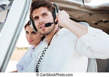 Portrait of young pilot and beautiful stewardess inside...