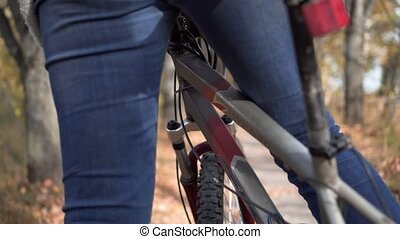 woman rides a bicycle through the woods. legs and wheel closeup