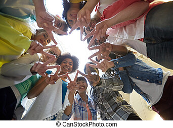 international students showing peace or v sign - education,...