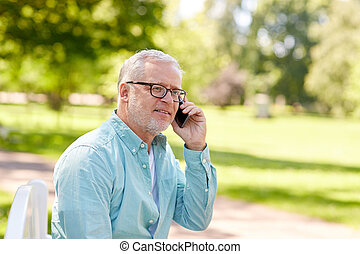 senior man calling on smartphone at summer park