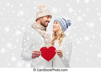 smiling couple in winter clothes with red heart - love,...