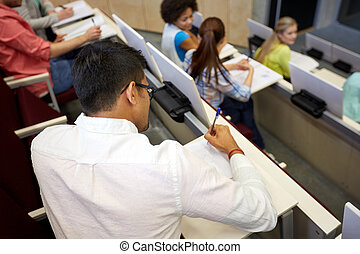 group of students with notebooks in lecture hall -...