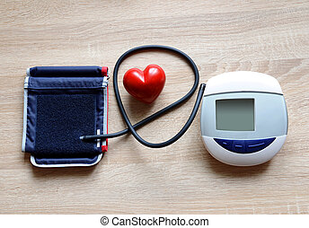 Digital Blood Pressure Monitor with heart on wooden...