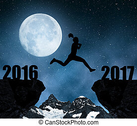 Girl jumps to the New Year 2017 in night.