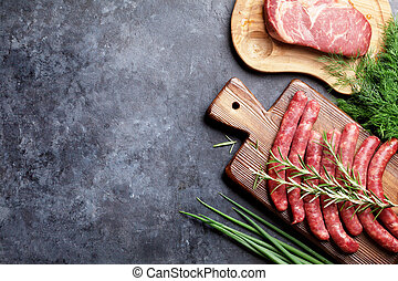 Sausages, meat and ingredients for cooking. Top view on...