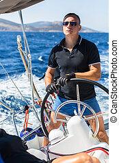 man skipper steers wheel sailing - Young man skipper steers...