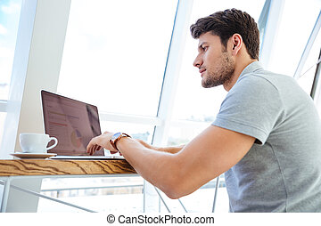 Handsome young man working with laptop while having coffee...