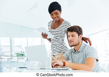 Two businesspeople working in office and discussing new ideas