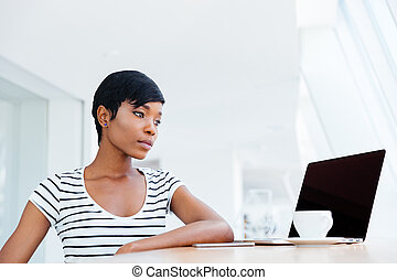 Serious attractive african businesswoman working with laptop...