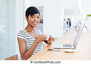 Portrait of a happy smiling african businesswoman using laptop