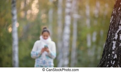 Smiling beautiful woman using mobile phone in park during...