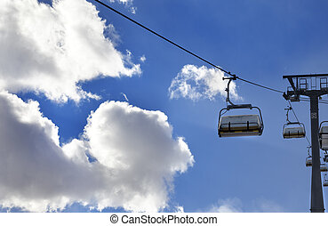 Chair-lift and blue sky with sunlight clouds at evening