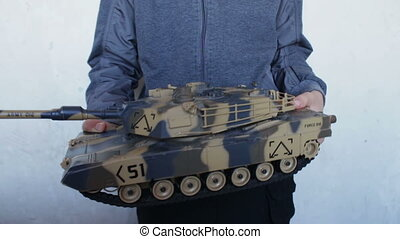 child holding a big toy tank in the hands with a call NO...