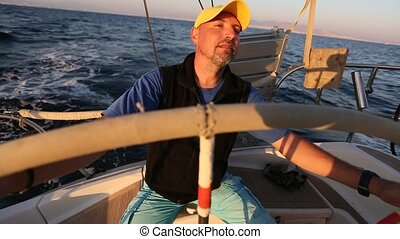 Yachtsman skipper during race, on his sailing yaht boat on...