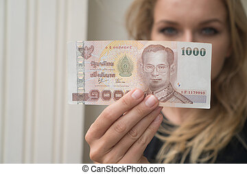 Woman holding 1000 Thai Baht note withdrawned from ATM -...