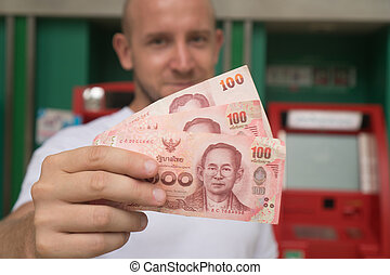 Man holding cash withdrawned from ATM - Closeup of 100 Thai...