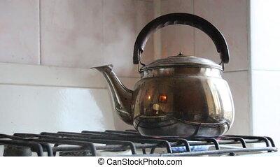 Simmering whistling kettle on the old stove. - Boiling...
