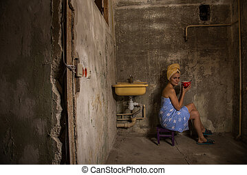 Cheap accommodation. Girl drinking tea in an old apartment