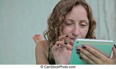 Young curly woman lying in the bed with tablet pc. Dolly...