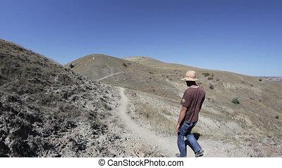 a man walking a dog is on the hills - a man in a straw hat...