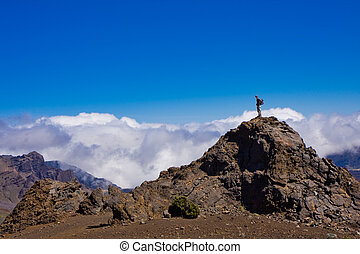 Hiking to the Top of the Haleakala Crater - A hiker is...