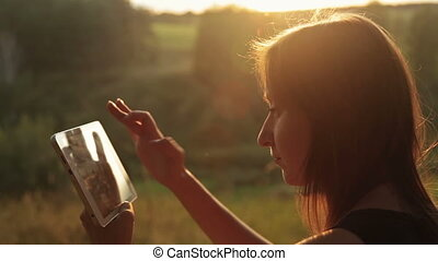 Woman using digital tablet in the forest at sunset - Woman...