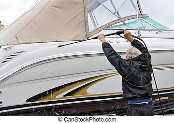 man using power washer on boat