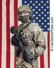 USA soldier with machine gun in hand and American flag on background