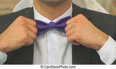 Stylish man tightening bow tie indoors - Stylish man...