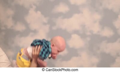 Dad tosses baby in the clouds