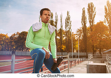 runner resting at sports arena