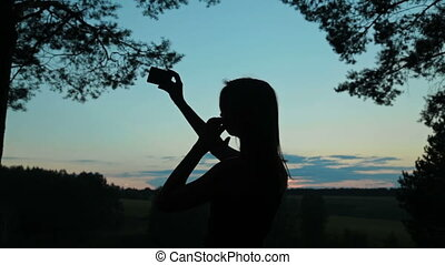 Silhouette of a young woman taking selfie with her phone after sunset