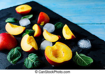 Slices of nectarines and peaches on blue wooden background....