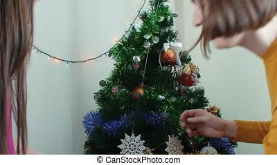 Two young women decorating Christmas tree small quarrel...