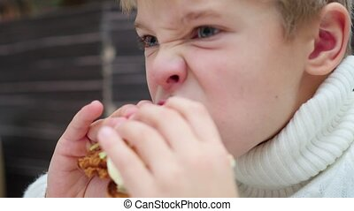 the kid eats a sandwich at a fast food restaurant closeup