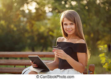 Girl with credit card and tablet pc.
