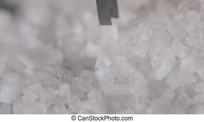 Welsh sea salt flakes on dark background. Close up of...