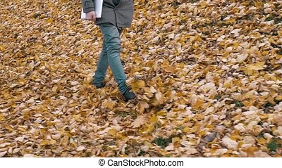 Portrait of a romantic man with beard walking into the forest autumm with tablet. Handsome student in park.