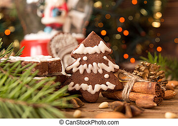 Christmas gingerbread cookies against background branch of...
